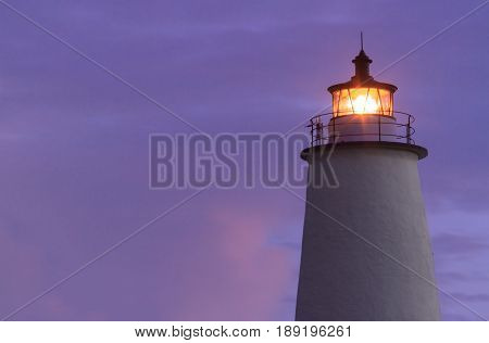 Th LIghthouse on Ocracoke Island shines agains a colorful North Carolina sky at dawn.