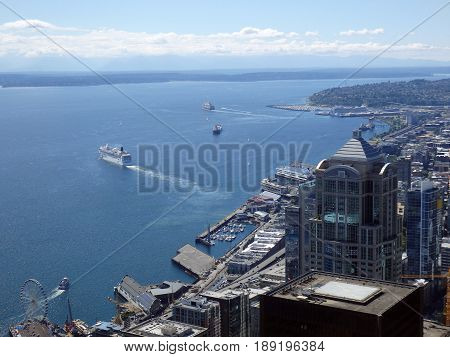 SEATTLE-- JUNE 25: Aerial view of Puget Sound with boats leaving harbor downtown Seattle buildings Wharf and Highway on June 25 2016 in Seattle WA.