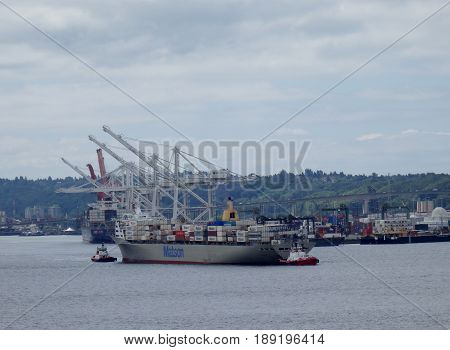 SEATTLE USA - JUNE 25 2016: Matson shipping boat towed into Seattle harbor to be unloaded by cranes in as tugboats pushes the boat.