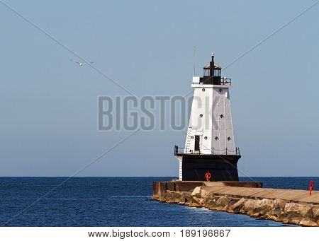 The Ludington Michigan North Breakwater Lighthouse rises from the brakwater with a seagull flying above the waters of Lake Michigan.
