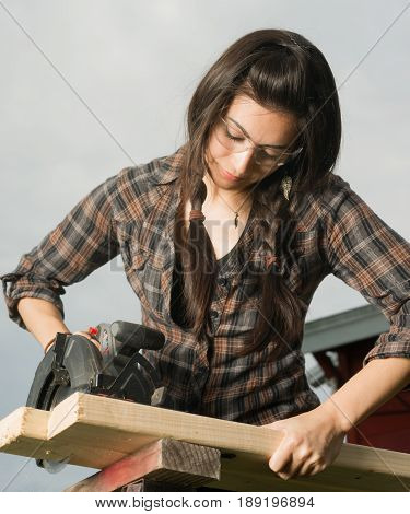Brunette woman in pigtails cuts 2x4 boards with battery operated saw