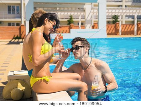 Party at smimming pool. Group of cheerful couples drinking cocktails in the pool. Guy tries to meet a girl