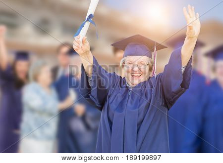 Happy Senior Adult Woman In Cap and Gown At Outdoor Graduation Ceremony.