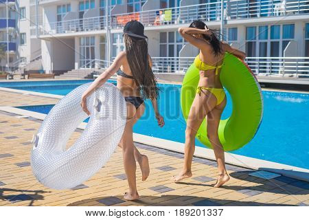 Two beautiful sexy hipster girls dancing with swimming circles near swimming pool. graceful beautiful figure and shape