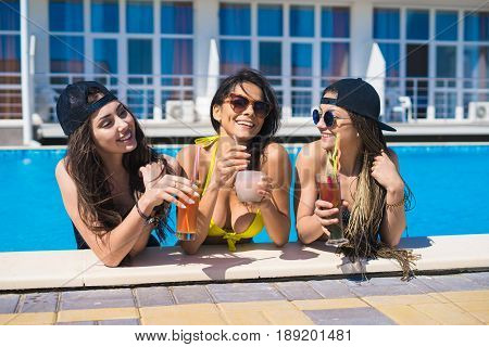 Party at smimming pool. Group of cheerful girls at the edge of the swimming pool drinking cocktails and laughing