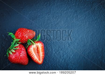 Ripe juicy strawberries on a stone table. Background with copyspace.