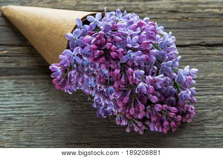 Lilac Flowers Bouquet In A Craft Paper Cornet On The Old Wooden Background