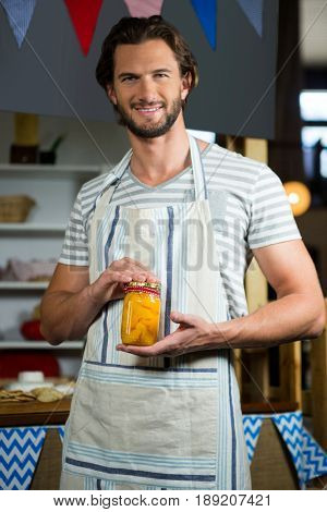 Portrait of smiling shop assistant holding a jar of pickle in grocery shop