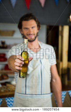 Portrait of smiling shop assistant holding olive oil bottle in grocery shop