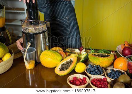 Shop assistant preparing papaya juice at health grocery shop