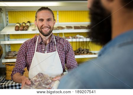 Portrait of smiling male staff holding a meat packet at counter in market