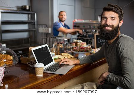 Smiling male customer using laptop while having coffee at counter in coffee shop