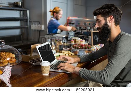 Male customer using laptop while having coffee at counter in coffee shop