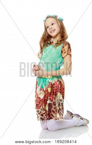 Beautiful little long-haired Caucasian girl posing in Studio.The girl knelt down.Isolated on white background.