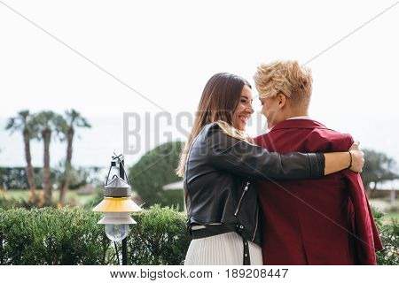 Back view of young cheerful lesbian couple embracing on urban background.