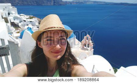 Brunette in straw hat taking a selfie on the background of Oia on Santorini island (Greece)