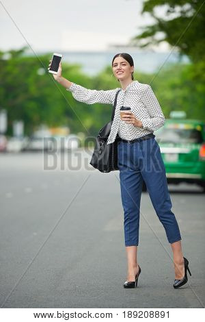 Beautiful young business lady with take-out coffee trying to catch a taxi in the street