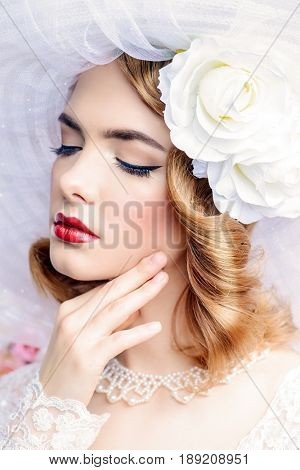 Close-up portrait of a charming bride in lace dress and elegant broad-brimmed hat. Wedding. Make-up and hairstyle. Beauty, fashion.