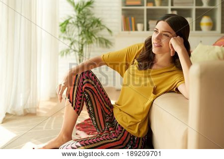 Beautiful young woman sitting on the floor at home and daydreaming