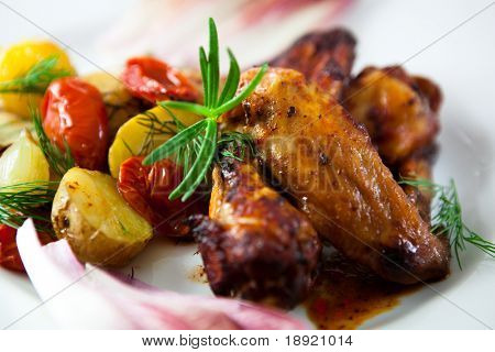 Roasted chicken wings with baked potatoes and tomatoes