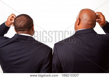 Confused African American Businessmen scratching their head.