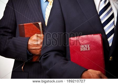 African American businessmen holding the Bible at work.
