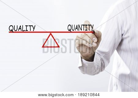 Businessman hand drawing Quality and Quantity balance - Business concept.