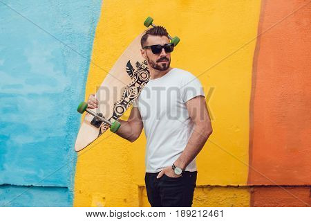 Stylish man in sunglasses and with a beard stands on the street with a long board. T-shirt mock up.