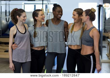 Group of smiling women standing together with arms around in gym