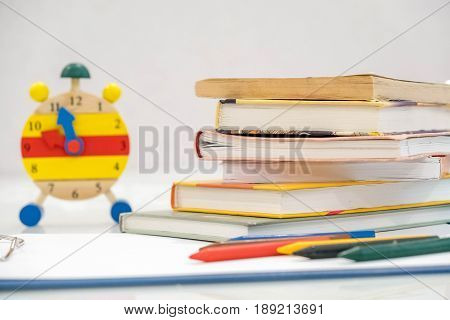 Back To School Background With Books And Alarm Clock Over Chalkboard