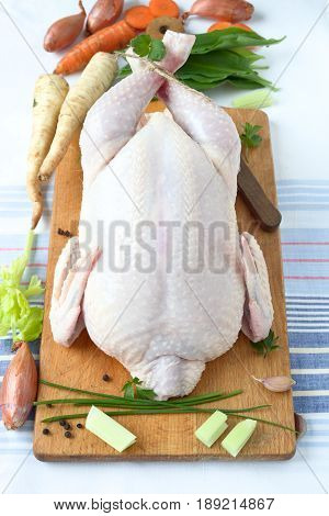 Whole raw chicken and vegetable on a wooden cutting board.