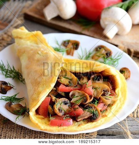 Vegetarian omelette idea. Fried mushrooms omelette with tomatoes and dill on a plate. Fresh mushrooms, tomatoes, dill on a vintage wooden background. Easy egg omelette. Rustic style. Healthy food
