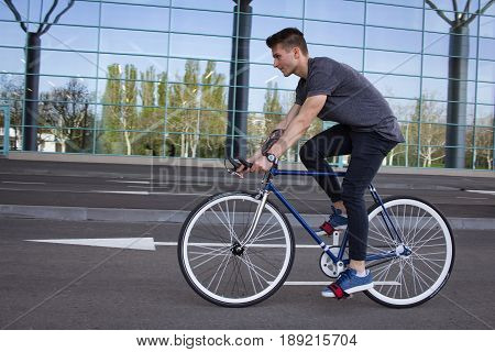 Young slim man rides a fixed gear bicycle on the empty road , hipster with tattoo on old black vintage bike on empty parking near big glass wall