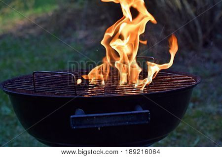 Charcoal grill with flames outdoors. Horizontal image.