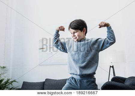 Smiling Little Boy Showing Biceps And Having Fun At Home