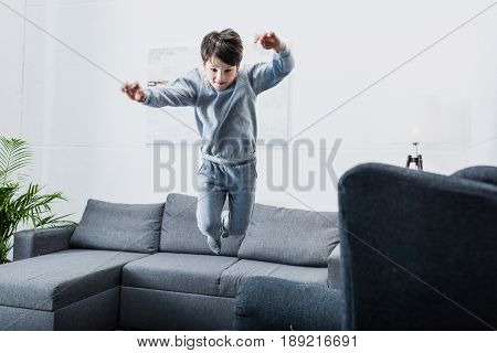 Cheerful Little Boy In Pajamas Jumping On Couch At Home