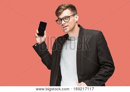 The young caucasian businessman in glasses on red studio background talking on cell phone