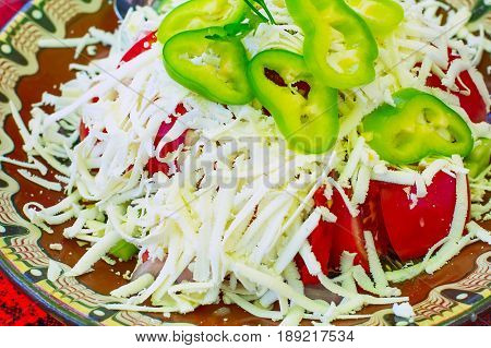 Bulgarian traditional Bulgarian Shopsky Salad or Shopska salata made of tomatoes, cucumbers and cheese on the bulgarian red tablecloth