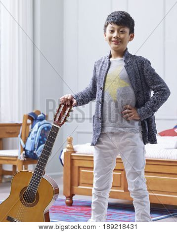 teenage Asian boy holding guitar, posing akimbo & smiling at camera