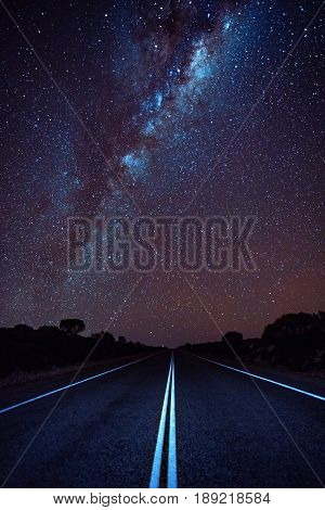 The Milky Way stretches across the night sky over an open road. Western Australia, Australia.