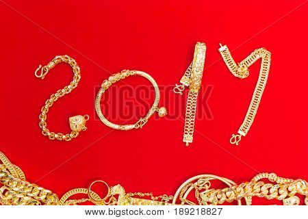Luxury beautiful golds pendant ornament accessory asian style is shape number 2017 years on red flannel background celebrating happy new year.