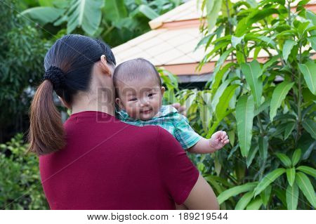 Asian cute new born baby smile happily with holding hands mother in the garden.