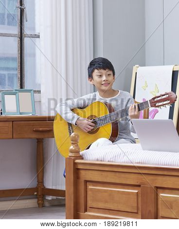 teenage Asian boy learning, practicing, playing guitar at home