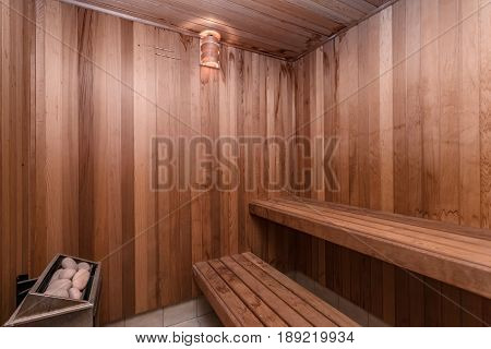 Interior of a home sauna with wood paneliing.