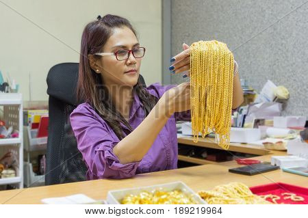 Asian mature woman smiling working in gold shop owner business.