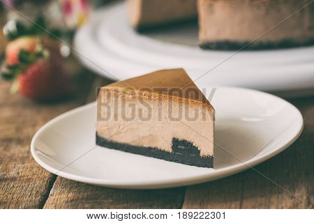 Homemade chocolate cheesecake on rustic wood table.Baked chocolate cheesecake on plate.Brownie cheesecake for coffee break or tea time in cafe.Triangle slice piece of chocolate cake in dramatic style. Dark chocolate brownie cheesecake.