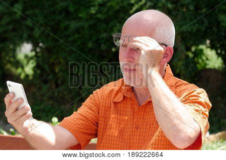 a mature man has problems with his eyesight for reading on his smart phone