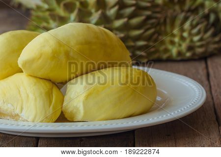 Traditional Thai fruit :Durian is the king of fruit in Thailand. Delicious durian on white plate put on rustic wood table. Durian is tropical fruit so delicious sweet and good smell. Ripe durian has yellow gold color.