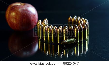 9mm bullets and a red apple on the black mirror background