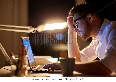 business, overwork, people, deadline and technology concept - stressed businessman in glasses with laptop computer typing at night office